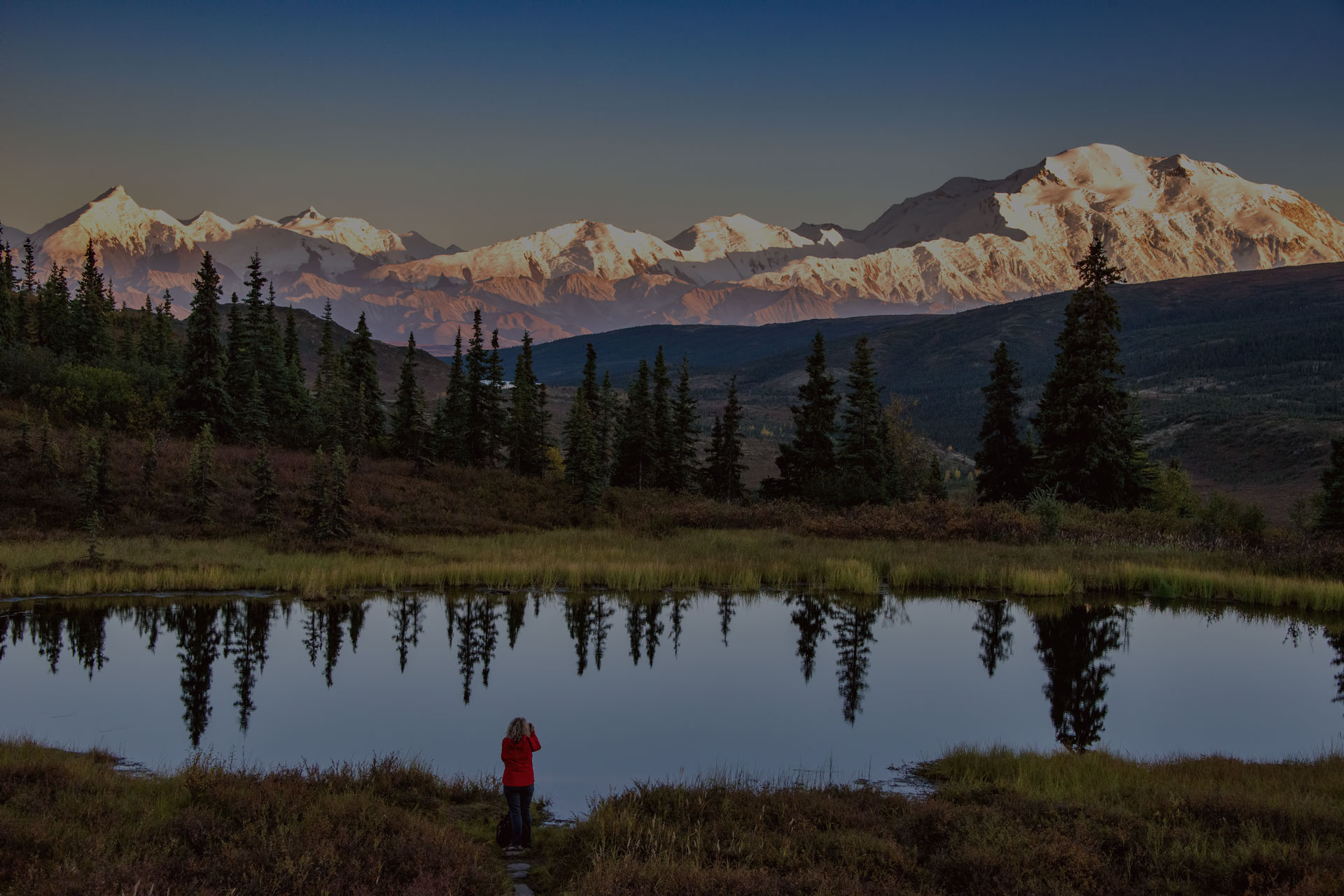 view of alaska's mount denali looms over calm pond at sunset